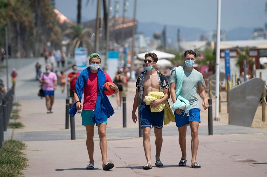 People walk along a beach in Barcelona on July 18, 2020.