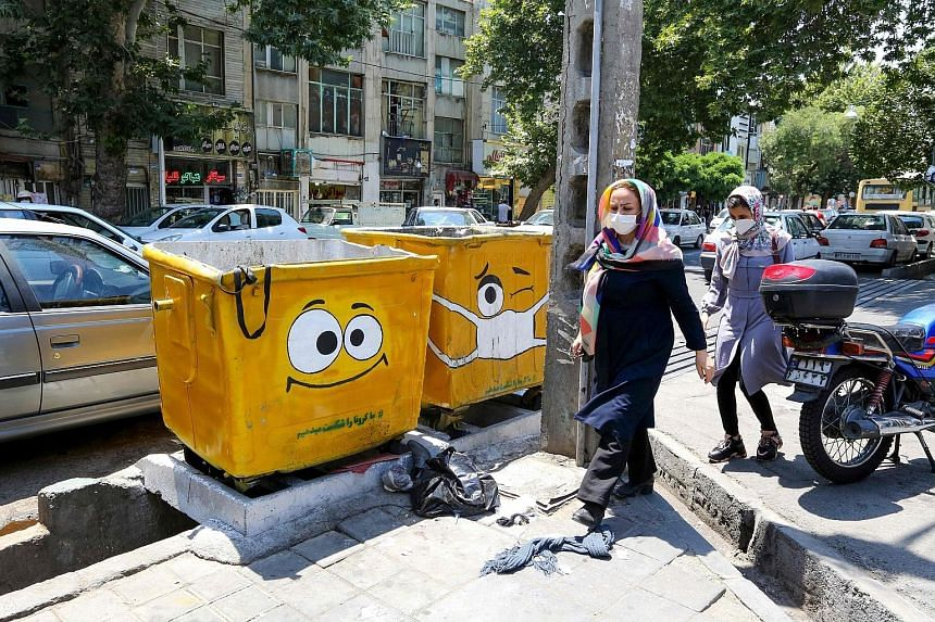 Iranians walking past street bins painted with drawings of sad or masked faces in a campaign to spread awareness of Covid-19, which has infected an estimated 25 million Iranians, with another 35 million at risk. PHOTO: AGENCE FRANCE-PRESSE Gravedigge