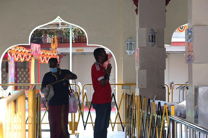 A devotee praying at Sri Mariamman Temple as a staff member disinfects and cleans the barricades. The temple has boosted online offerings for devotees through the live streaming of daily morning and evening prayers since March.