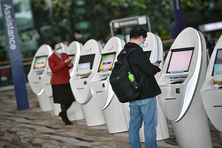 Automated kiosks at Changi Airport fitted with proximity touch screens. Seven out of the 15 people ST asked would wait for a vaccine to be found before travelling by plane.