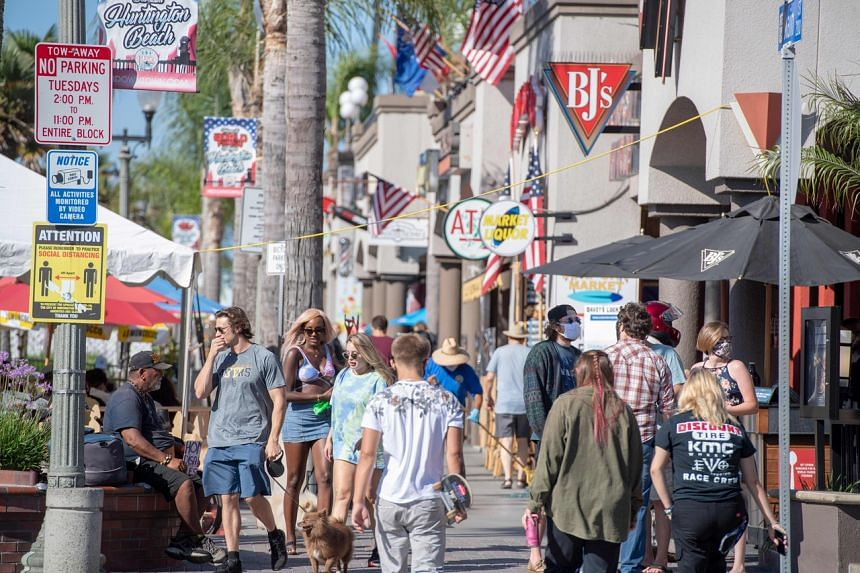 A sign (left) advising people to maintain social distancing is seen in Huntington Beach, California, on July 16, 2020.