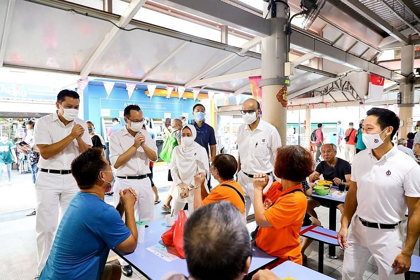 Senior Minister Tharman Shanmugaratnam (standing, second from right) with fellow Jurong GRC MPs (from left) Shawn Huang, Tan Wu Meng, Rahayu Mahzam and Xie Yao Quan speaking to patrons during a visit to a hawker centre in the constituency to thank re