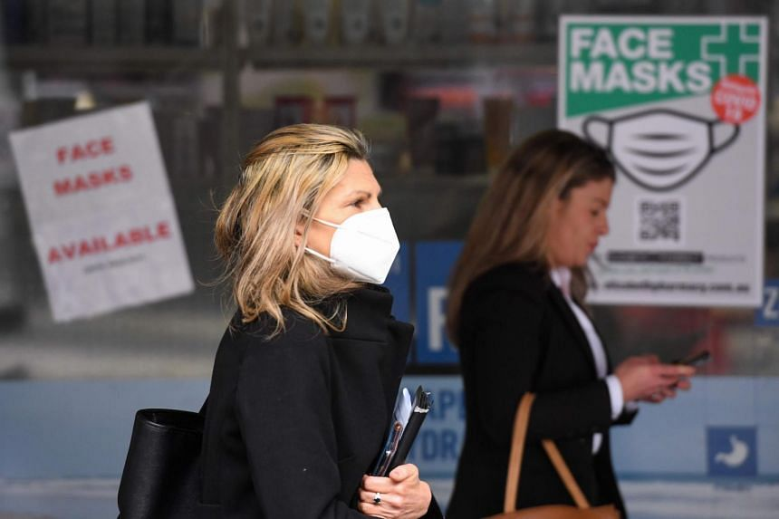 People walk past a sign advertising masks in Melbourne on July 20, 2020.