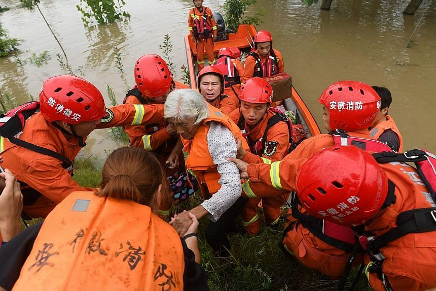 Rescue workers evacuating a flood-affected resident near the Wangjiaba dam on the Huai River in China's Anhui province on Tuesday.
