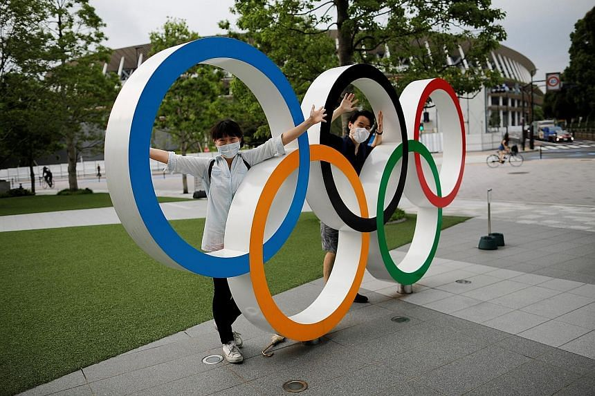 The Olympic rings outside the National Stadium in Tokyo continue to draw visitors despite the Games' postponement. A poll has revealed that under a quarter of Japanese are in favour of the city holding the Olympics in 2021.
