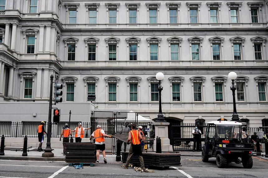 Workmen erect a protective fence around the Eisenhower Executive Office Building on June 5, 2020.