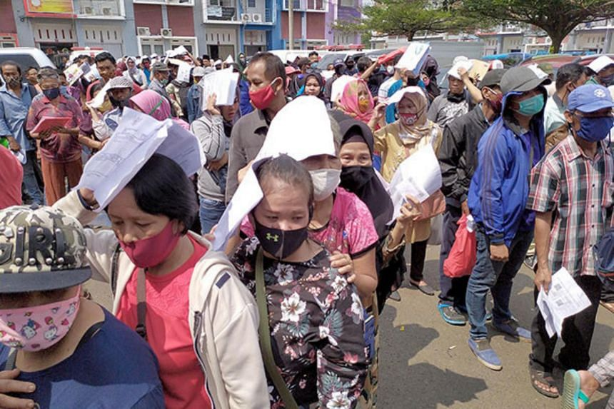 Residents wait for their turn to receive social assistance money at the Bogor regency administration office complex in West Java on July 20, 2020.