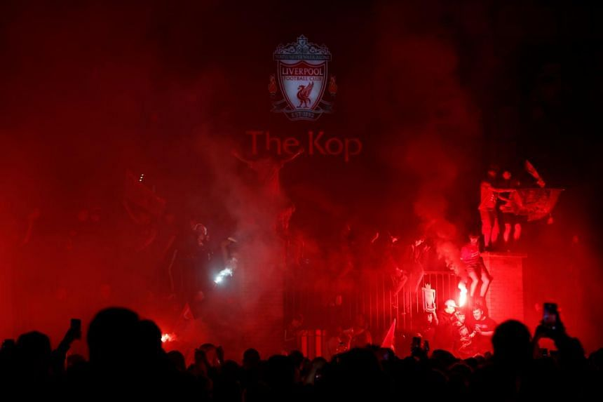 Liverpool fans celebrate with flares outside Anfield stadium on July 22, 2020.
