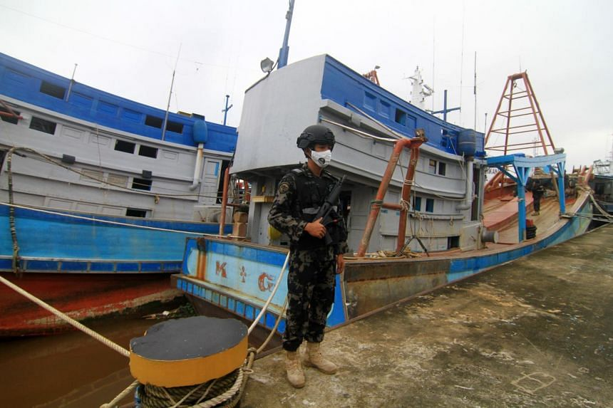 An Indonesian officer from the Maritime Affairs and Fishery Ministry stands guard next to two seized Vietnamese fishing boats in Sungai Rengat, Kubu Raya, West Kalimantan.
