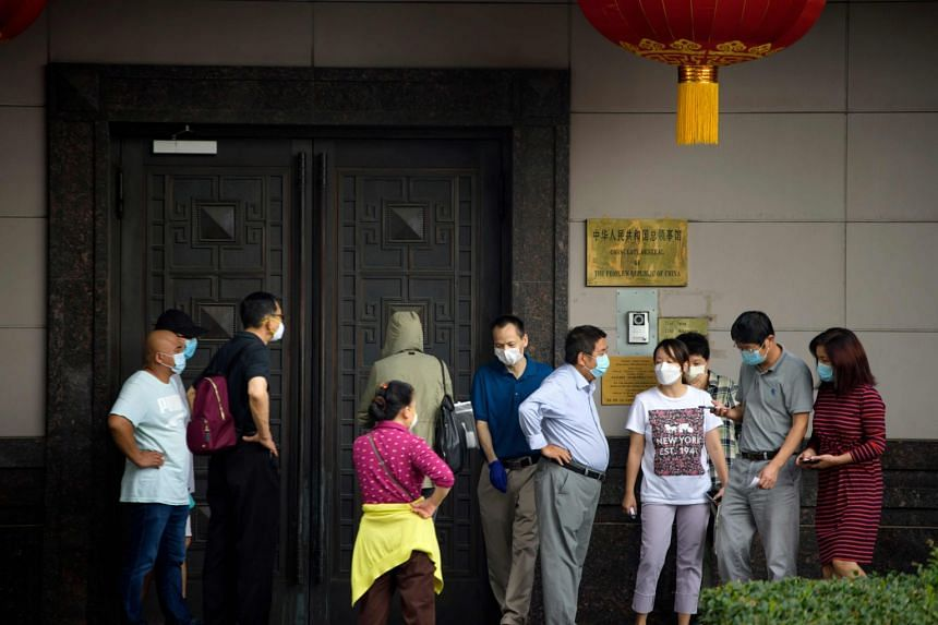 People attempt to talk to someone at the Chinese consulate in Houston on July 22, 2020.