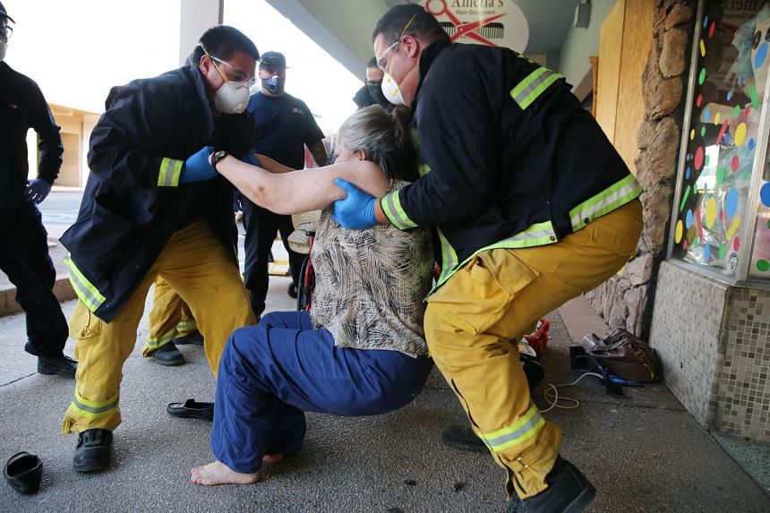 US fire department personnel help a woman who fell from her wheelchair amid the Covid-19 pandemic in hard-hit Imperial County, California.