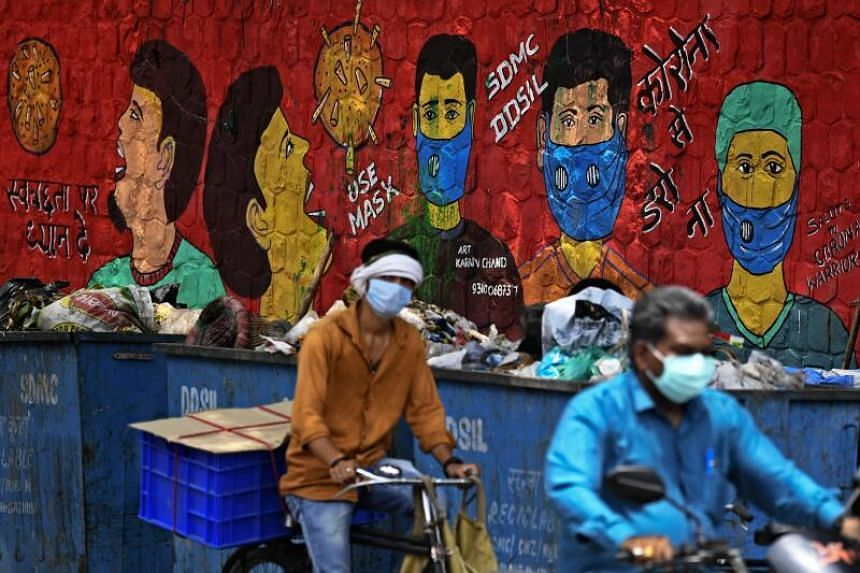People ride past a mural on coronavirus in New Delhi, on July 23, 2020.