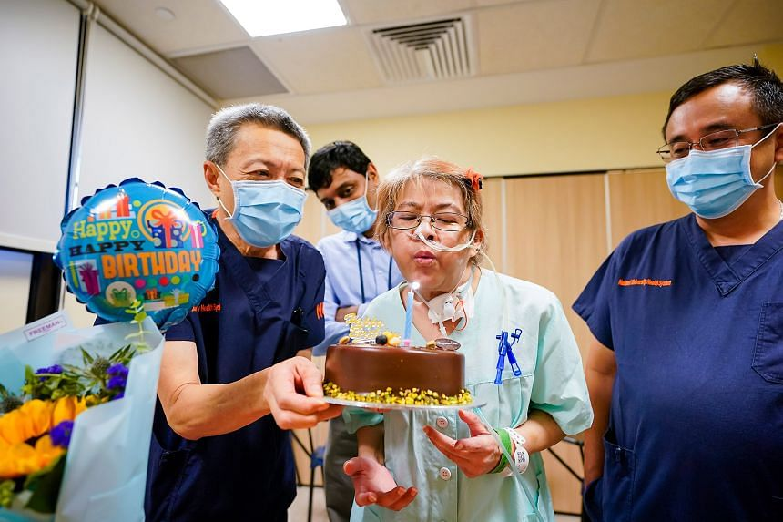 Madam Choy Wai Chee, who turns 58 today, celebrating her birthday in the National University Hospital on Friday, with the staff and doctors who tended to her.