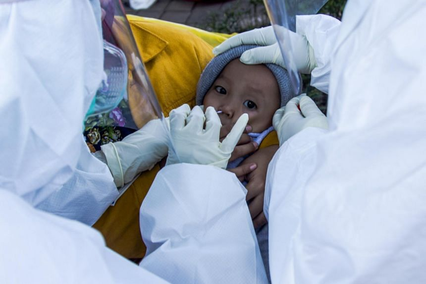 Health care workers collect specimen samples from a child during a Covid-19 swab test in Surabaya, on July 20, 2020.