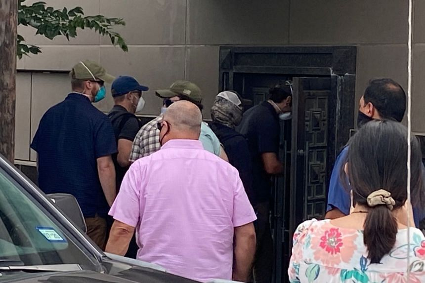 A group of people use power tools to pry open a rear door of the Chinese consulate in Houston.