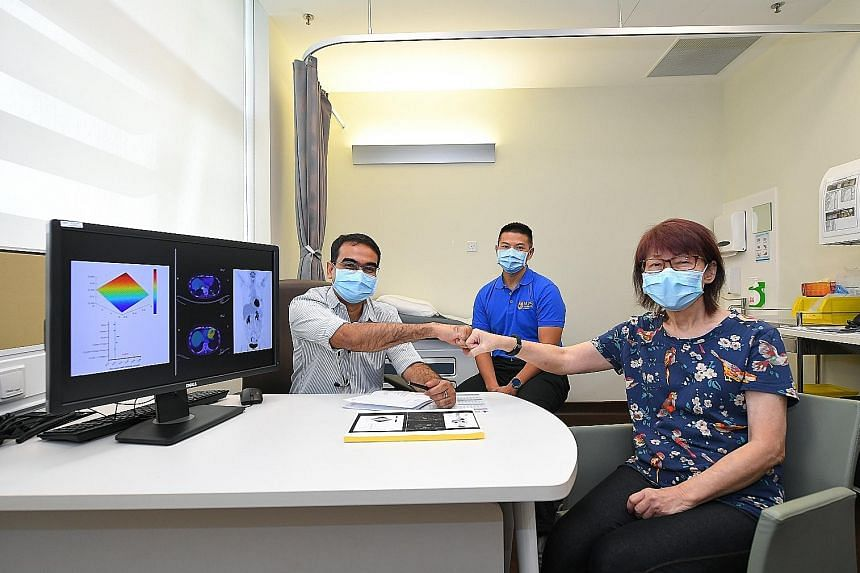 Madam Peggy Tay, whose cancer is in remission after taking the drug combination suggested by AI platform QPOP, fist bumping her oncologist Anand Jeyasekharan, who treated her at the National University Cancer Institute, Singapore. With them is Associ