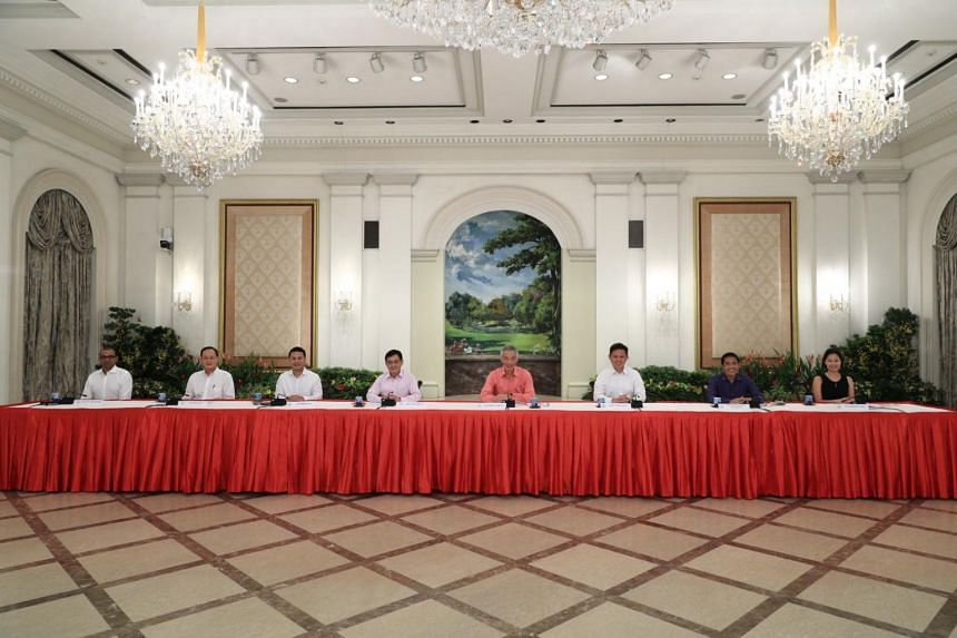 PM Lee (centre) announced his new Cabinet at a press conference on July 25, 2020. With him were (from left) Dr Janil Puthucheary, Dr Tan See Leng, Mr Desmond Lee, Mr Heng Swee Keat, Mr Chan Chun Sing, Dr Maliki Osman and Ms Gan Siow Huang.