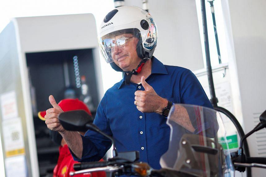 Brazil's President Jair Bolsonaro prepares to ride a motorcycle in Brasilia on July 25, 2020.