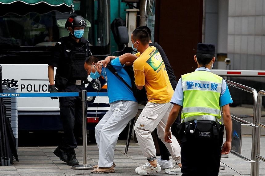 Far left: Police officers detaining a man who tried to display a sign outside the US consulate in Chengdu. Left: People leaving the consulate in Chengdu yesterday. PHOTOS: REUTERS A worker removing a sign at the entrance to the United States consulat