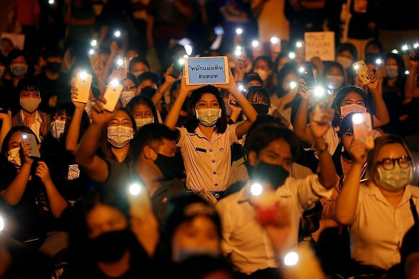 Demonstrators, some wearing their school uniforms, lighting up their devices during a protest last Thursday demanding the resignation of Thailand's Prime Minister Prayut Chan-o-cha.