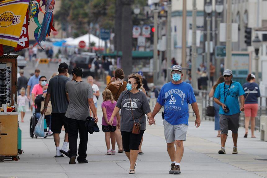 People walk along the ocean pier in Huntington Beach, California, on July 23, 2020.