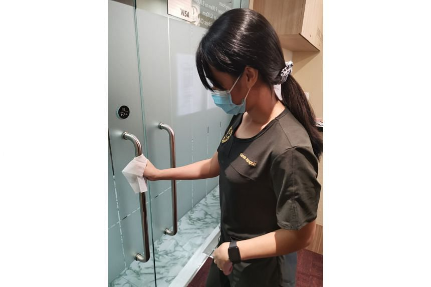 Ms Eefah Alsagoff, a clinic assistant at the International Centre for Thoracic Surgery, wiping the clinic's door handles. A wipe-down of the common area, door handles and sofa is done after each patient leaves the clinic.