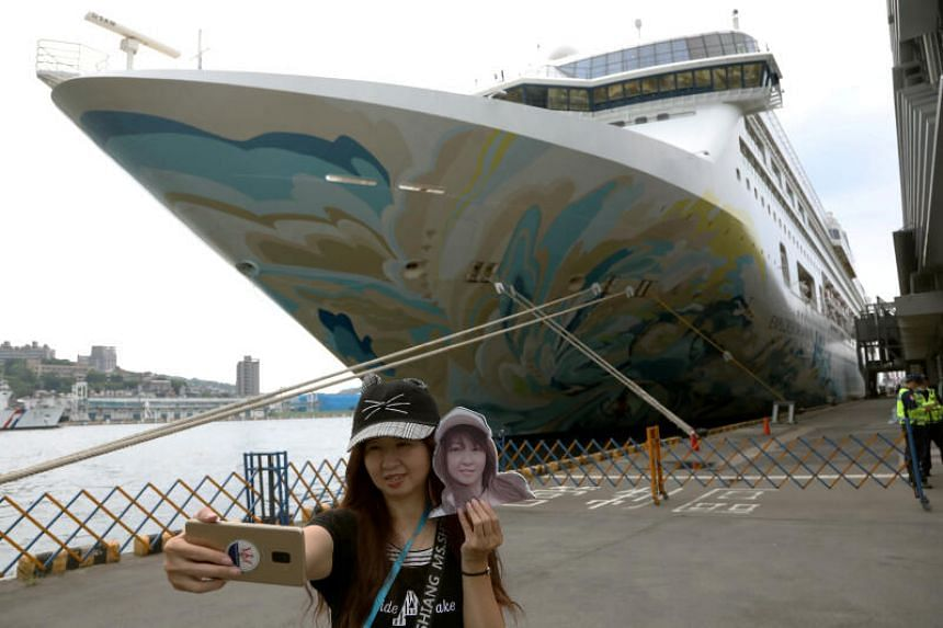 A woman takes a selfie in front of the Explorer Dream cruise ship, in Keelung, Taiwan, on July 26, 2020.