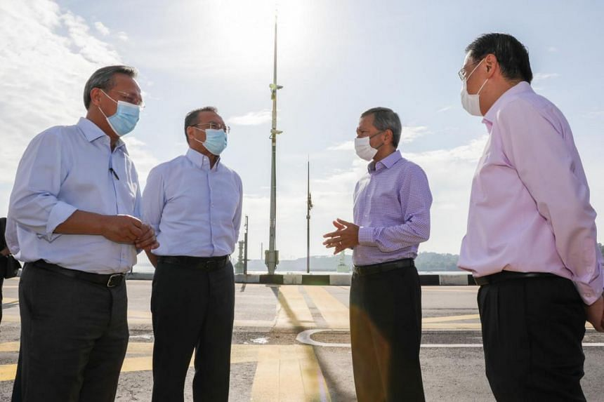Minister for Foreign Affairs of Singapore Dr Vivian Balakrishnan (second from right) and Minister of Foreign Affairs of Malaysia Dato' Seri Hishammuddin Tun Hussein (second from left) at the Causeway on July 26, 2020.