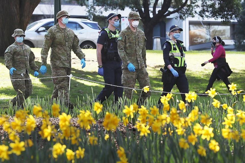 Soldiers and police officers patrolling the streets of Melbourne at the weekend. Australia's Covid-19 death toll rose to 155 yesterday and Victoria state reported more than 450 new infections in 24 hours.