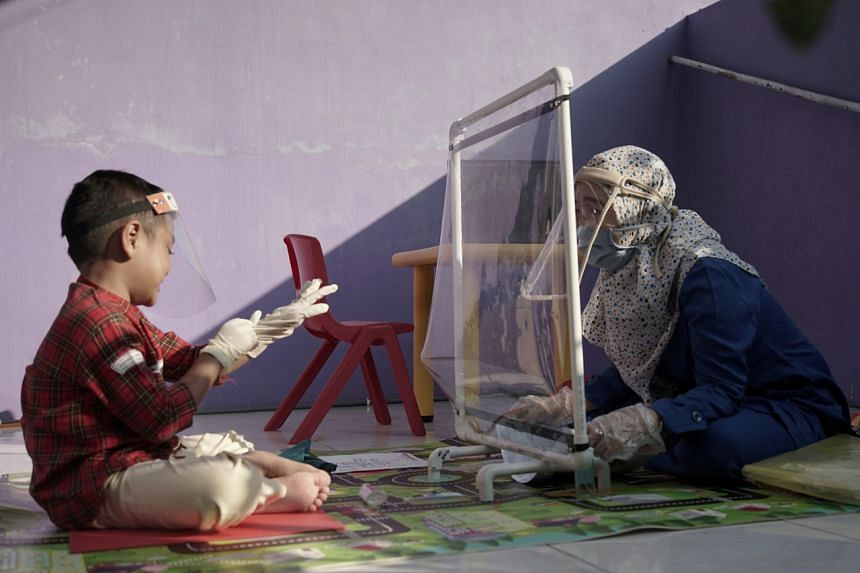 A teacher talks through a plastic barrier during a visit to a pupil's house in Semarang on July 22, 2020.