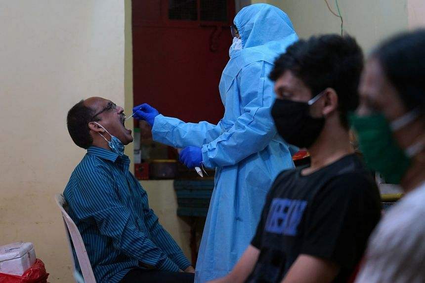 A healthcare worker takes a swab from a man to test for Covid-19 in Mumbai on July 24, 2020.