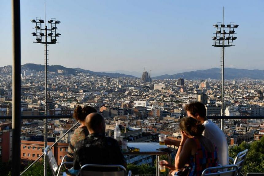 People sit at a terrace bar overlooking the Sagrada Familia in Barcelona on July 25, 2020.
