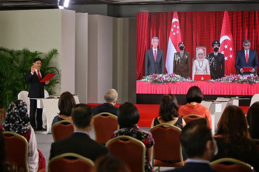 Deputy Prime Minister Heng Swee Keat in Parliament House with live screen projection of (from left) Prime Minister Lee Hsien Loong, President Halimah Yacob and Chief Justice Sundaresh Menon at the Istana on July 27, 2020.