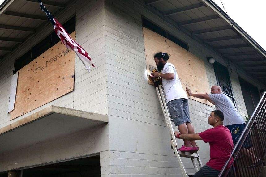 Residents board up the windows of their home in preparation for hurricane Douglas in Honolulu, Hawaii, on July 25, 2020.