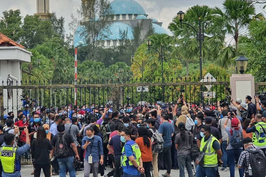 """A crowd gathers in front of gates to the court complex, shouting """"Hidup Bossku""""."""