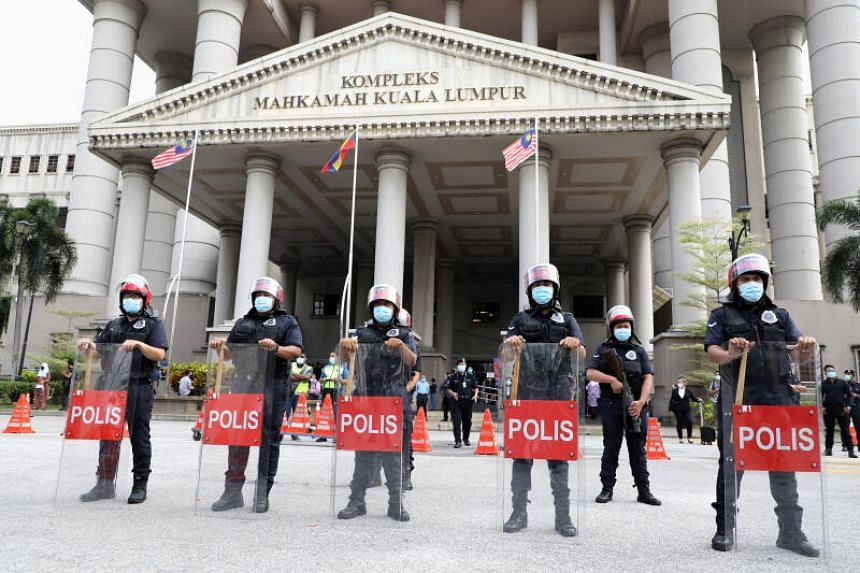 Police officers stand guard outside Kuala Lumpur High Court on July 28, 2020.