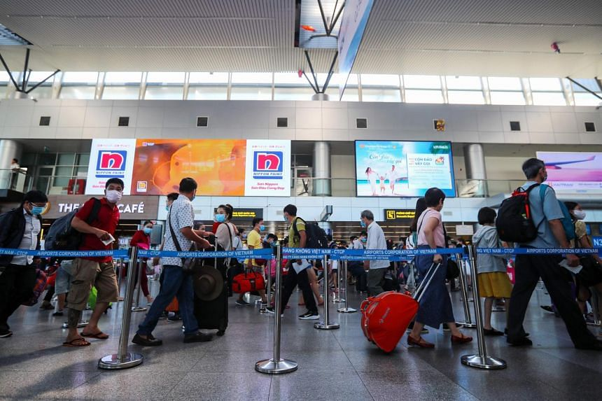 Passengers queue up for check-in at the departure terminal in Danang International Airport on July 27, 2020.