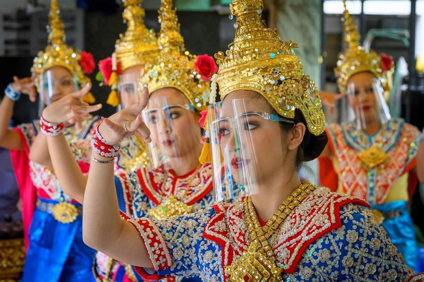 Traditional dancers wearing protective face shields perform at the Erawan Shrine in Bangkok on May 4, 2020.