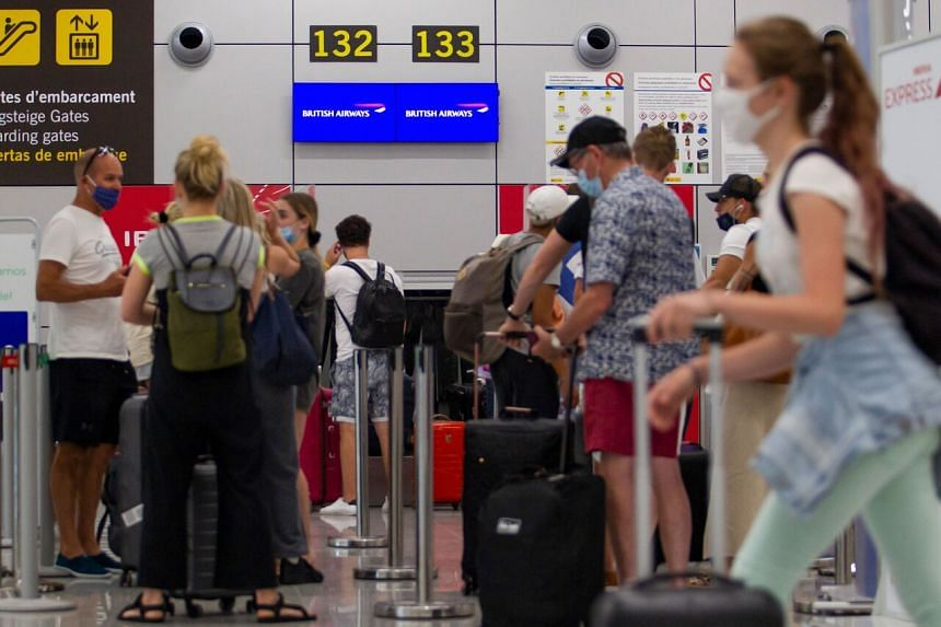 British tourists wait to check in for a flight to London at the airport in Palma de Mallorca on July 27, 2020.