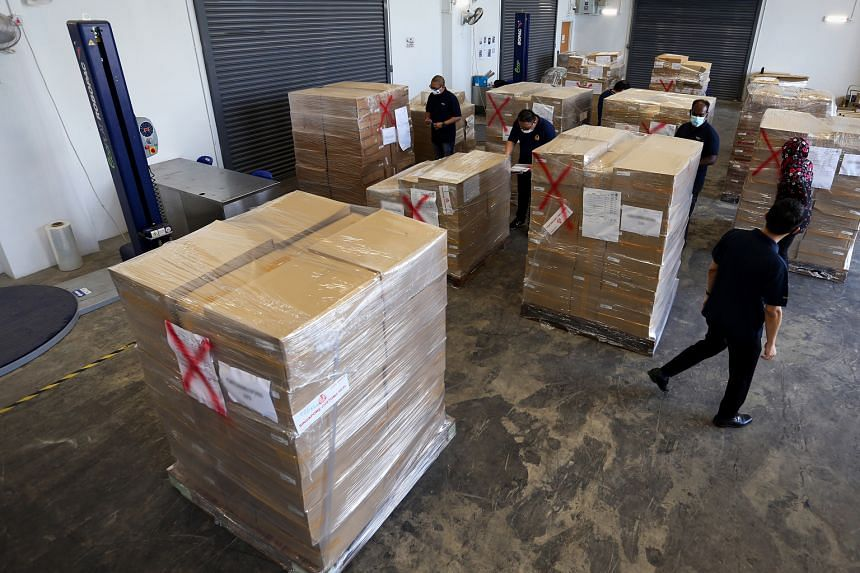 Above: Customs officers raiding a Woodlands flat last month. A Chinese national was arrested with 1,000 cartons of contraband cigarettes hidden in metal boxes. The illegal cigarettes had been declared as tea. The officers had been monitoring the ship
