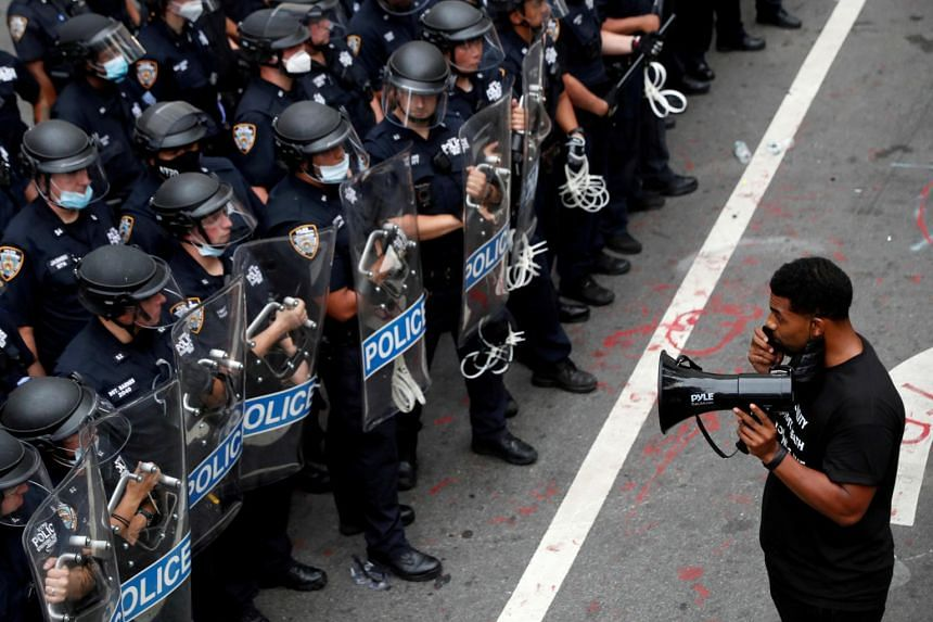 A demonstrator stands in front of New York Police Department officers in New York City, US, on July 1, 2020.