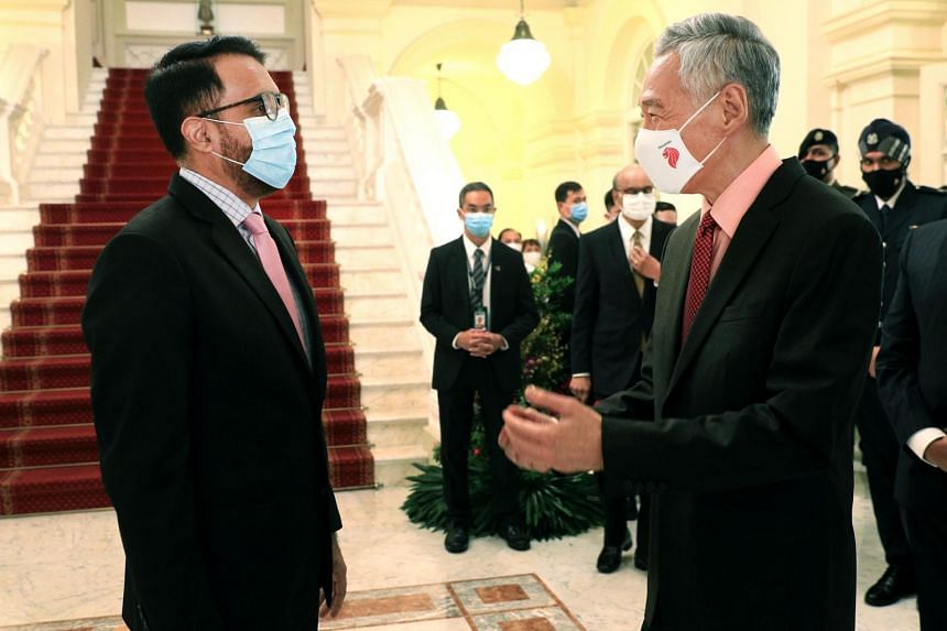 Workers' Party chief Pritam Singh speaks with PM Lee at the Istana on July 27, 2020.