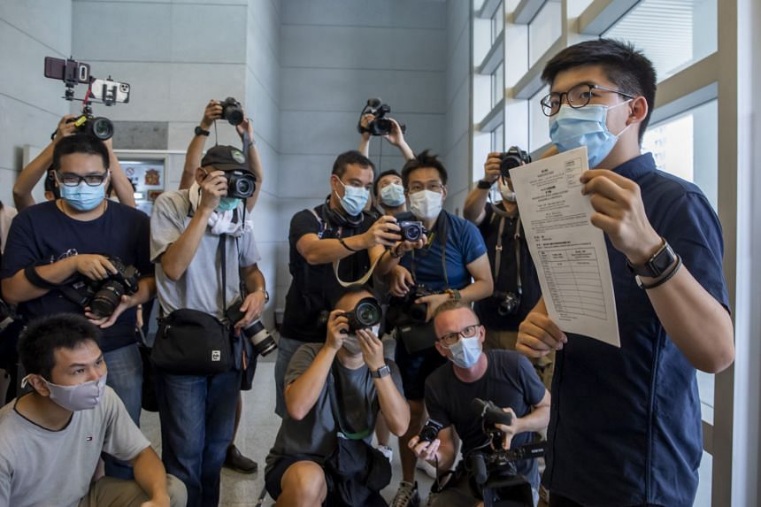 Pro-democracy activist Joshua Wong showing the media, on July 20, his application to run in this year's Legislative Council election in Hong Kong. Yesterday, reports emerged that the September vote could be postponed by a year, as the city's authorit
