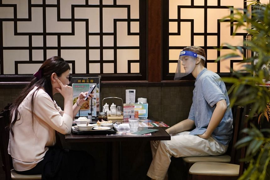 A woman sitting across from a mannequin used to enforce social distancing at a restaurant in Tokyo, which recorded 266 cases yesterday.
