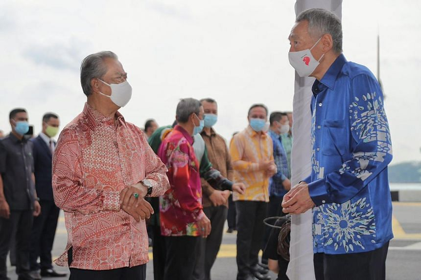 Malaysian Prime Minister Muhyiddin Yassin and Prime Minister Lee Hsien Loong at the international boundary line on the Causeway on July 30, 2020.