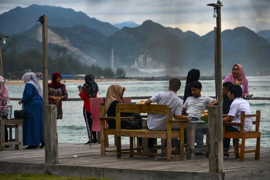 People gather at a cafe which reopened for visitors along a beach at Lhoknga, Aceh province on July 19, 2020.