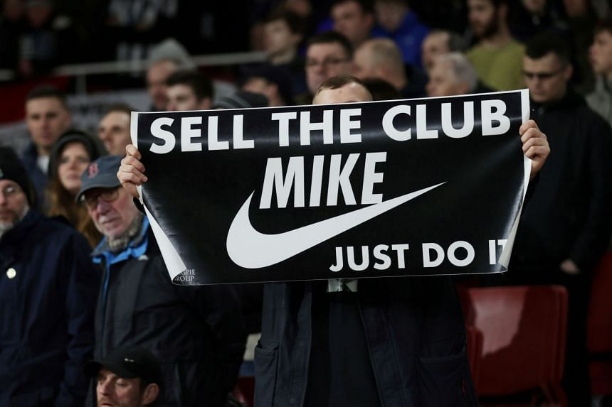 A fan displays a banner in reference to Newcastle United owner Mike Ashley during a February 2020 match.