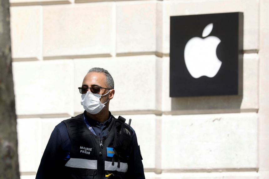 A municipal police officer walks past the Champs-Elysees Apple store in Paris, France, in April 2020.