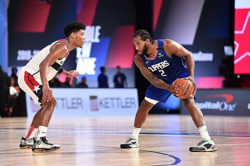 Los Angeles Clippers' Kawhi Leonard, facing Jerome Robinson of Washington Wizards during their NBA scrimmage ahead of the restart of the NBA season. For Leonard, their upcoming games are all about building chemistry among the players after the long l