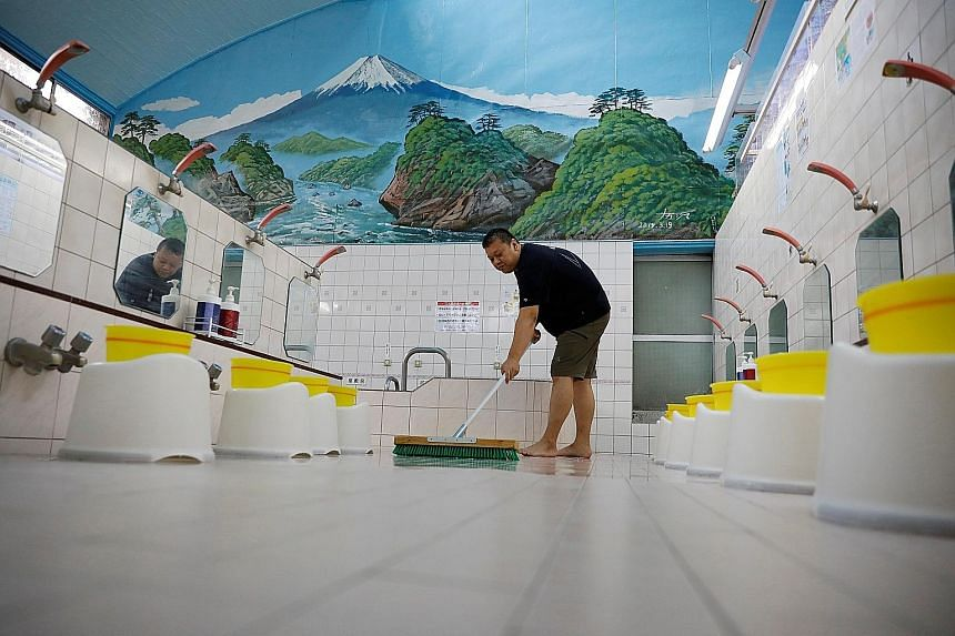 Mr Takuya Shimbo, the third-generation owner of Tokyo bathhouse Daikoku-yu, cleaning the floor before the bathhouse opens for the day.